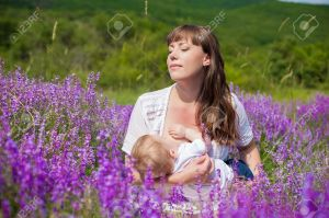 16715519-Mother-breastfeeding-her-baby-in-a-field-of-purple-flowers--Stock-Photo